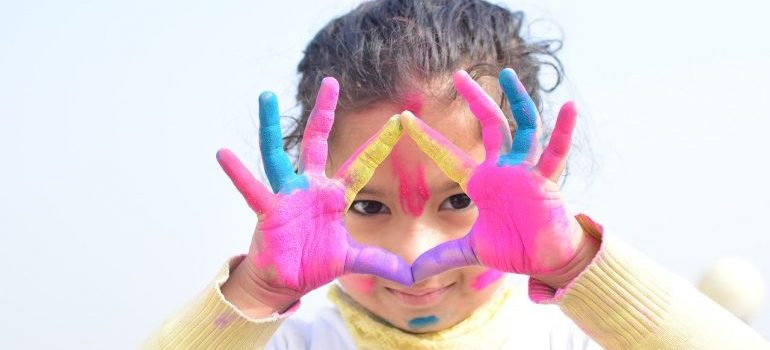 A girl with paint on her hands.