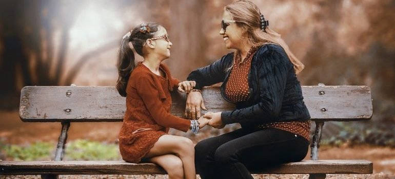 A mother and daughter sitting on a bench and talking.