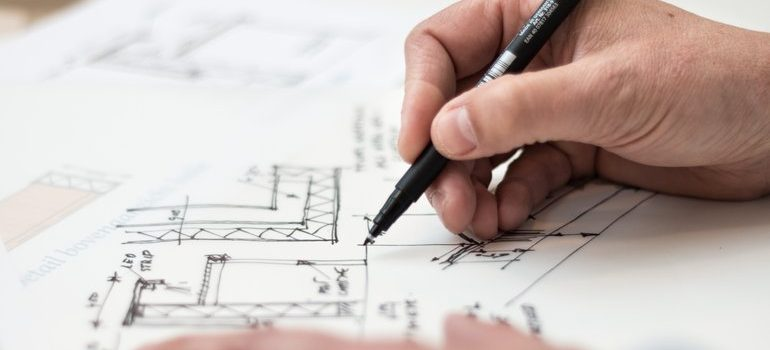 A person using house plans for moving bulky items.