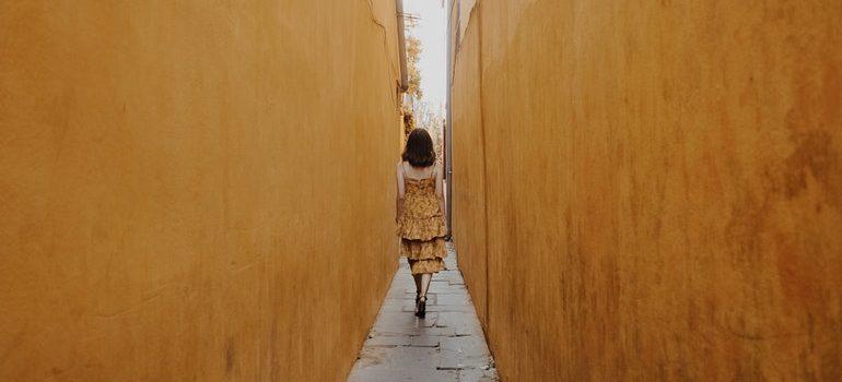 Woman walking between buildings.
