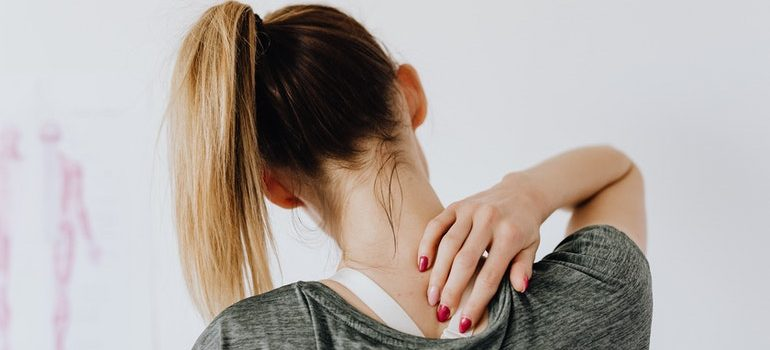 Person massaging their neck to avoid moving day injuries.