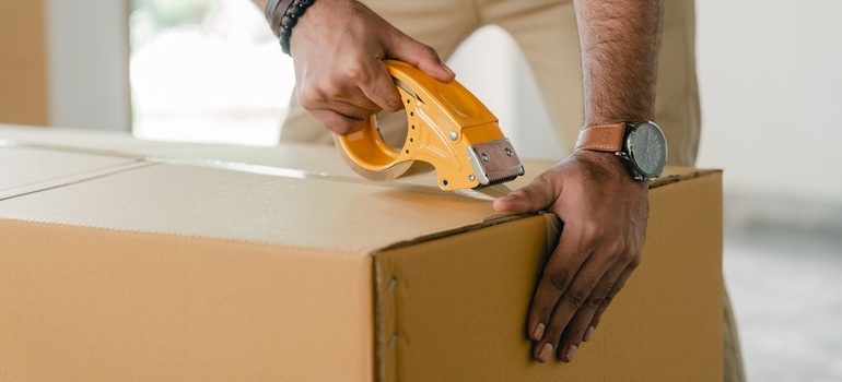 Person taping a box used to protect fragile items during transport.