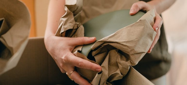 Person wrapping a dish in paper.