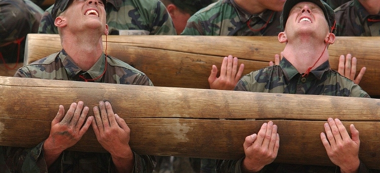 Group of soldiers lifting heavy logs