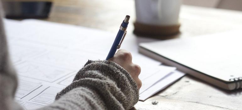A hand writing a list