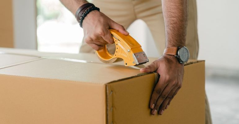 Person packing a box for storage