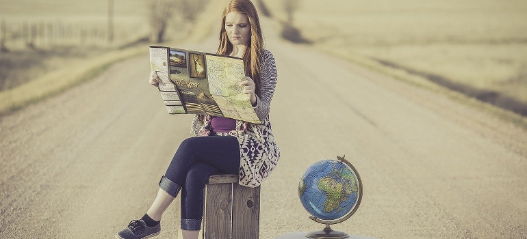 a woman sitting on the road and looking at a map