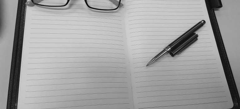 an empty notebook with a pen and glasses