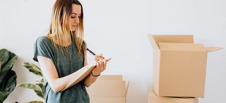 woman-writing-moving-boxes-behind