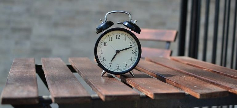 An alarm clock on a table to look at in order to save time while packing for moving.