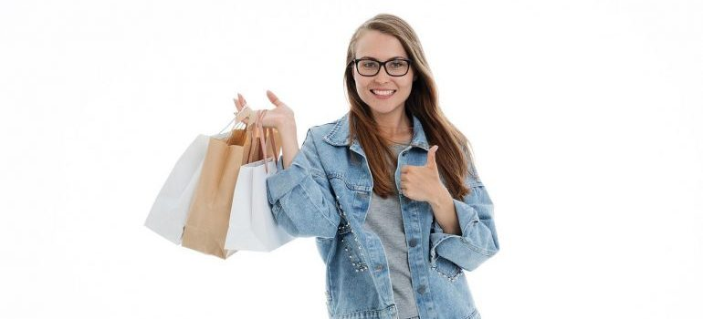 A girl holding shopping bags and giving a thumbs up.