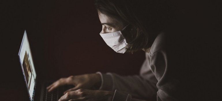 A woman wearing a mask trying to find reliable movers during the pandemic