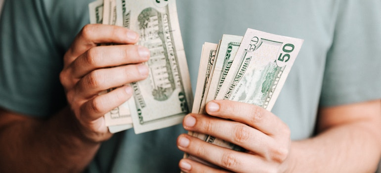 A man counting money trying to decide whether buying vs. renting warehouse is financially the right choice for his business.