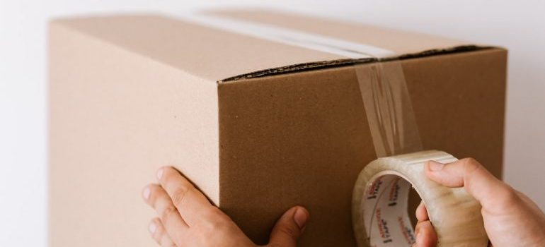 Person packing a box for moving during Coronavirus pandemic