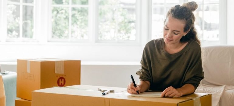 woman preparing for the move, writing a list on the cardboard box