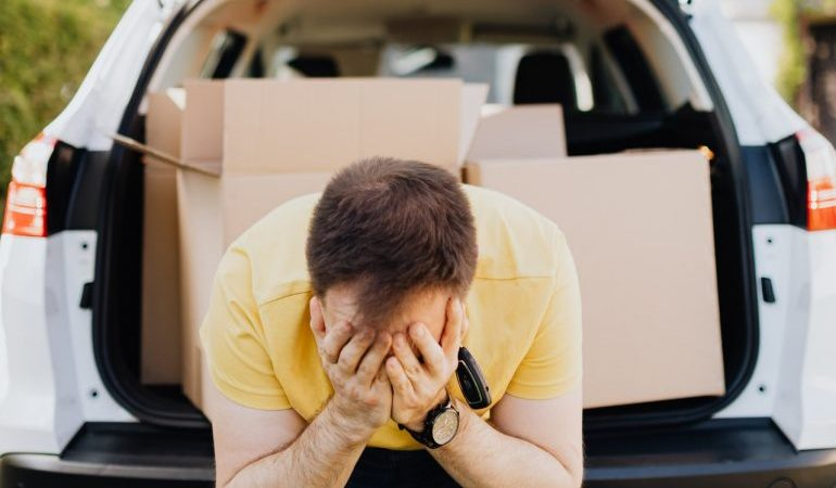 A man with his head in his hands, with moving boxes in the trunk of his car.