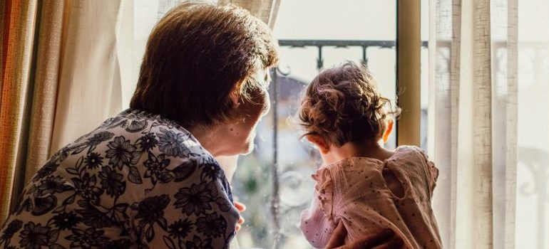 older woman with a baby near window