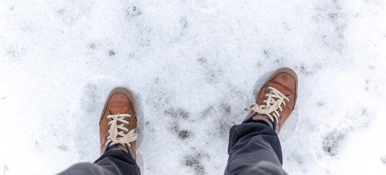 A man standing on ice in winter boots.