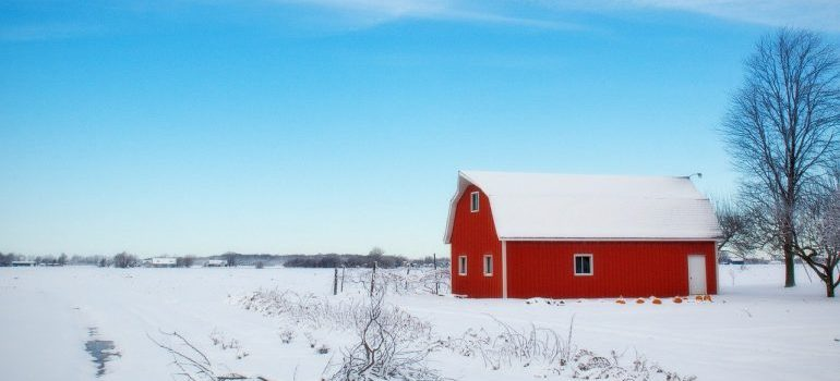 A red barn in the middle of a snowy field.