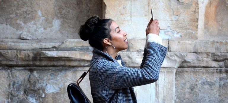 A woman holding a phone and taking a photo.