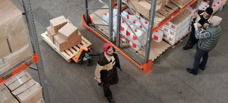 Three me inside a warehouse