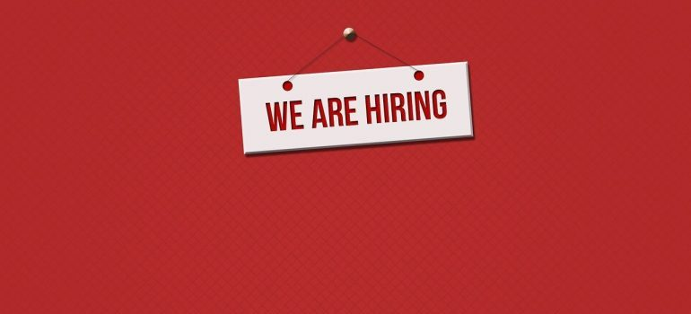 A we are hiring sign on a red surface.