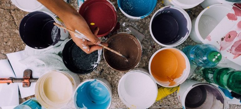 A person working with cans of paint.