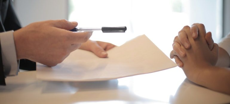 Person signing a contract after following tips for selling your Boise home.