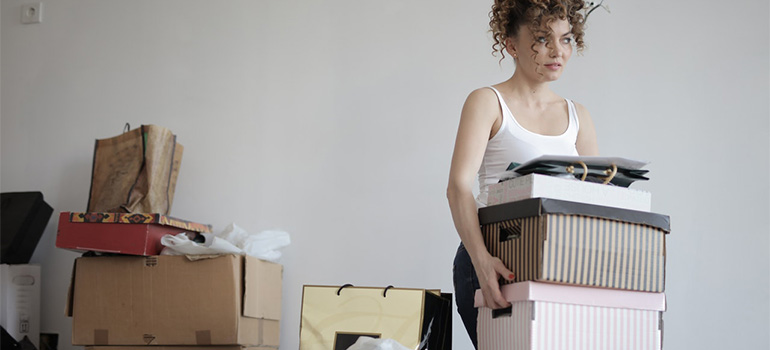 A woman carrying boxes, sharing your wish to repurpose your at-home storage spaces