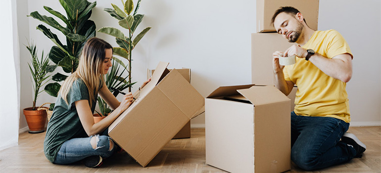 A girl and a guy packing boxes
