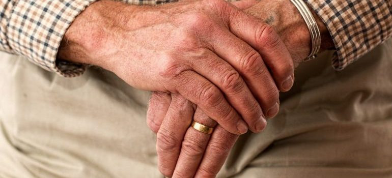 An elderly person with crossed hands.