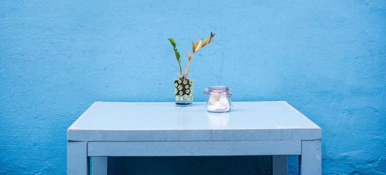 A blue table in front of a blue wall.