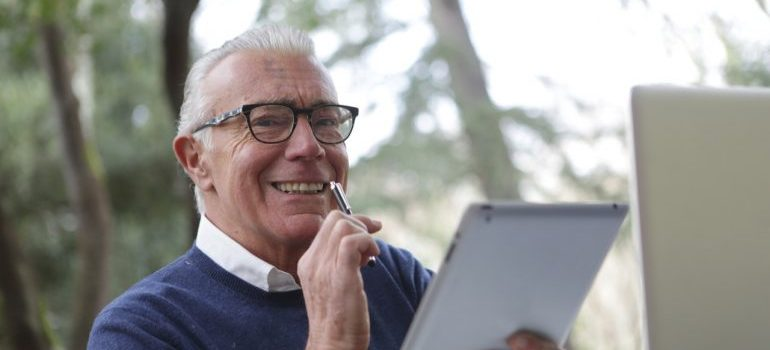 Smiling elderly man holding a pen and a tablet