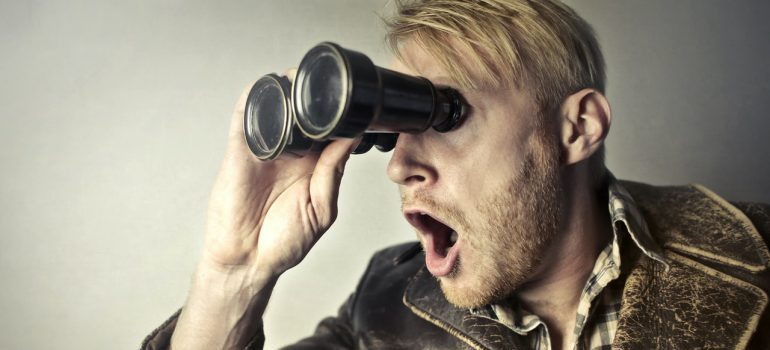 A surprised man using binoculars