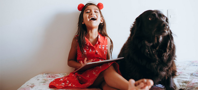 A girl sitting on a bed with a black dog, smiling and holding abook
