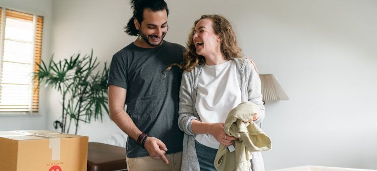 Couple smiling while unpacking boxes