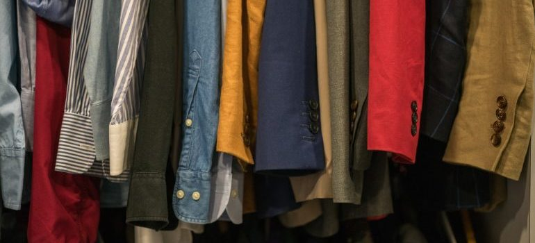 Shirts of different colors in a closet.