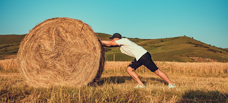 A man pushing a hay stack