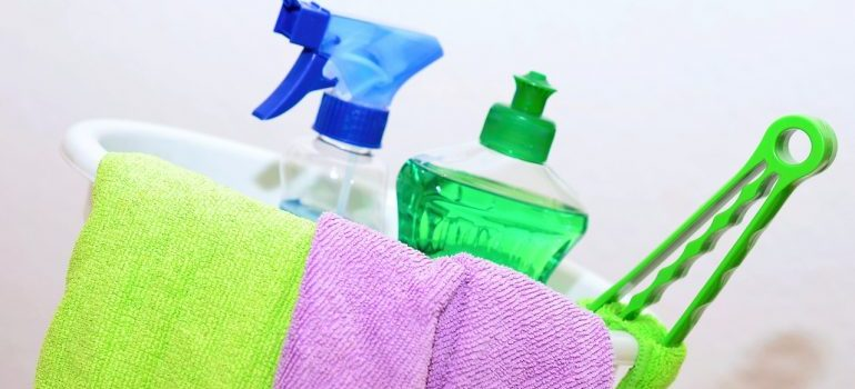 A bucket full of cleaning supplies to use before moving your fridge.
