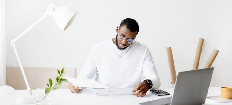A man in white calculating expenses before buying a vacation home overseas