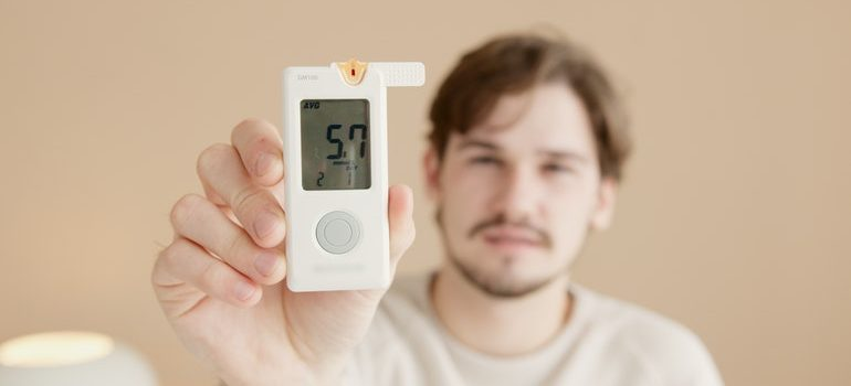 Man demonstrating one of the Self storage qualities his unit has with a thermostat showing 57 degrees Fahrenheit.