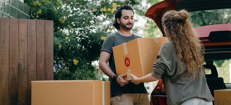 Man helping a woman with moving boxes.