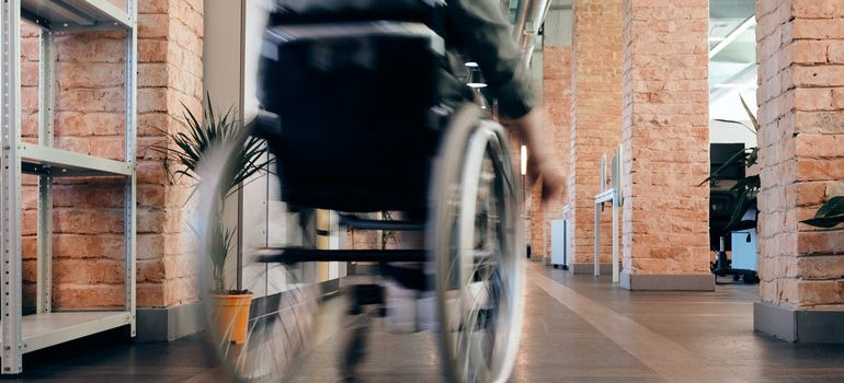 Person in a wheelchair racing down a hallway.