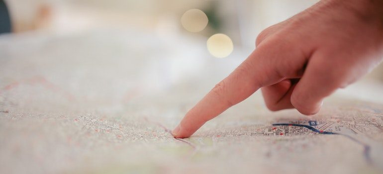 Finger pointing at a location on a map.