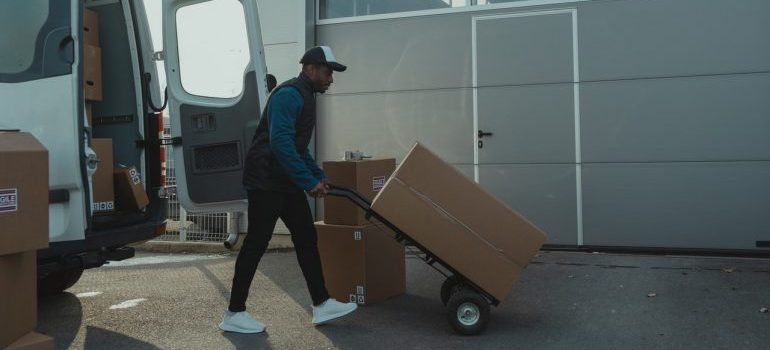 A person using dolly to move boxes.