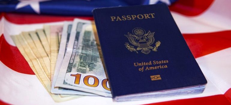A passport on the US flag and some dollar bills.