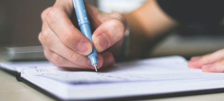 man writing down an inventory list