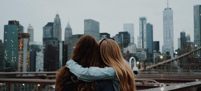 Two people hugging each other while looking at city skyline.