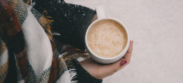 A woman holding a cup of coffe in the snow.