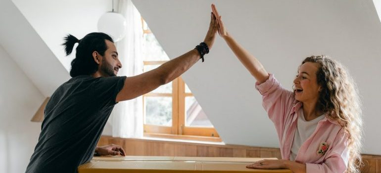 Young couple high fiving each other.